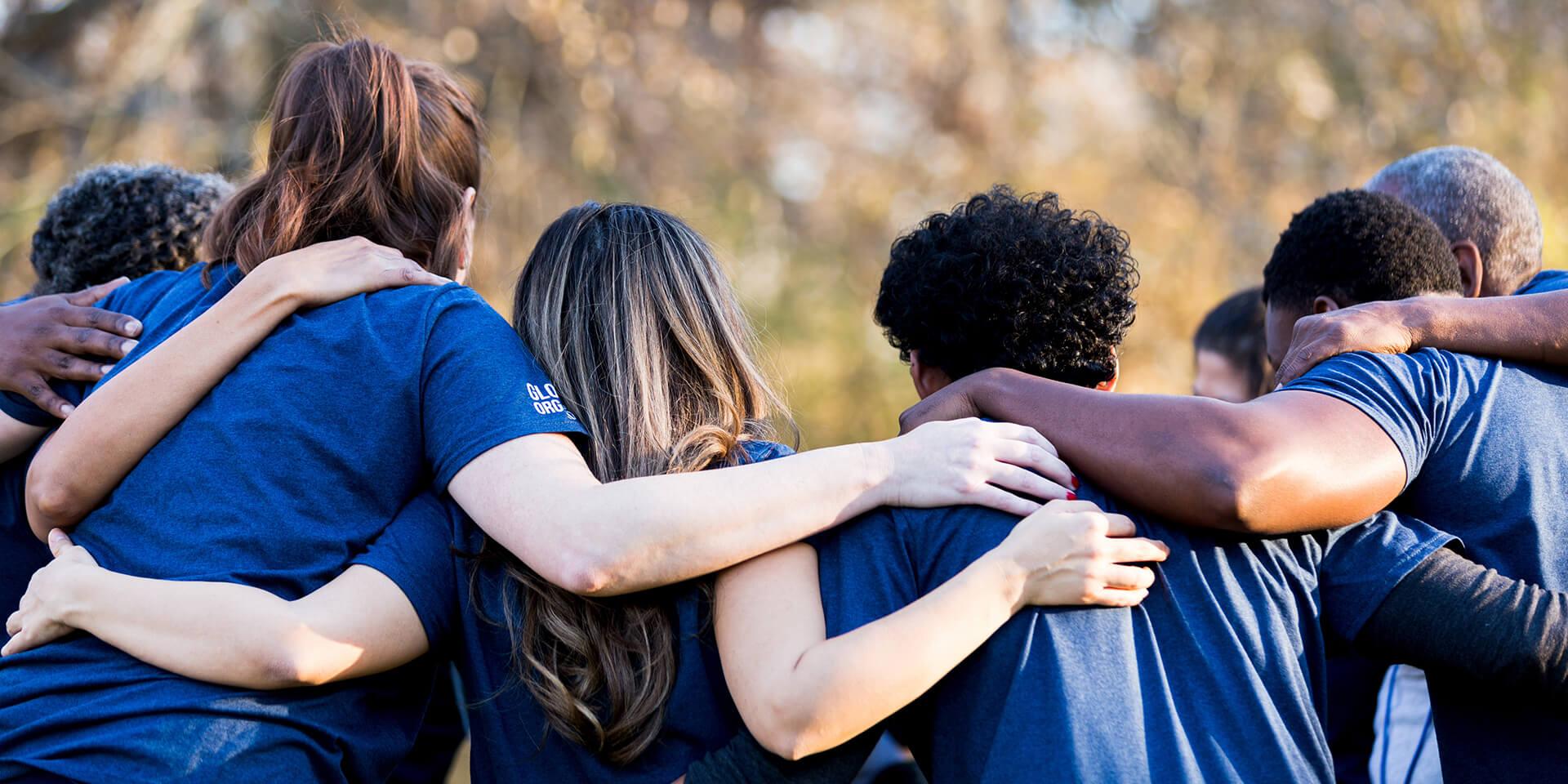 Eine Gruppe von Menschen legt die Arme umeinander