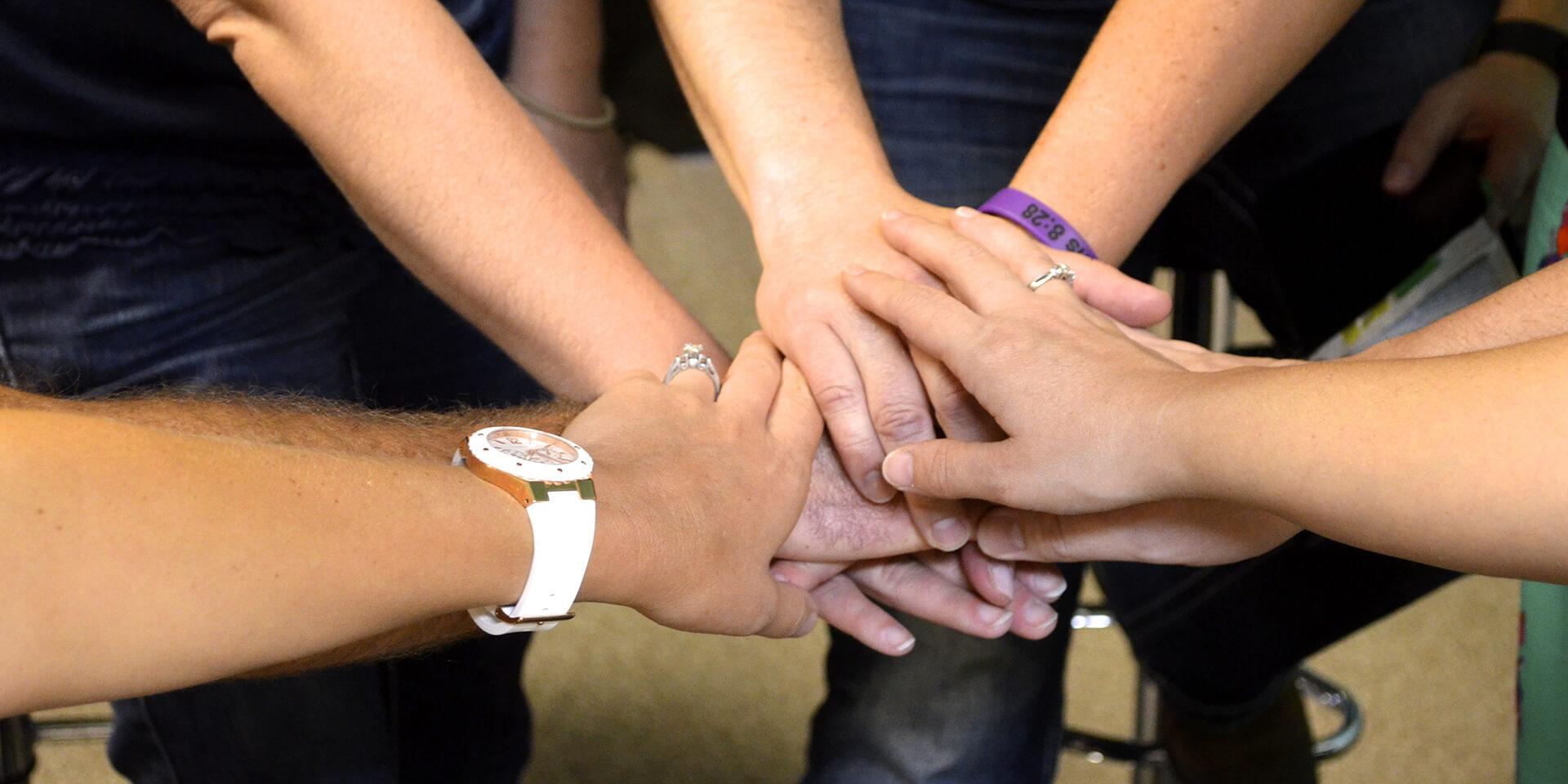 Eine Gruppe legt die Hände in ihrer Mitte aufeinander